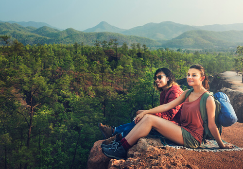 two travelers sitting on a cliff overlooking lush forest