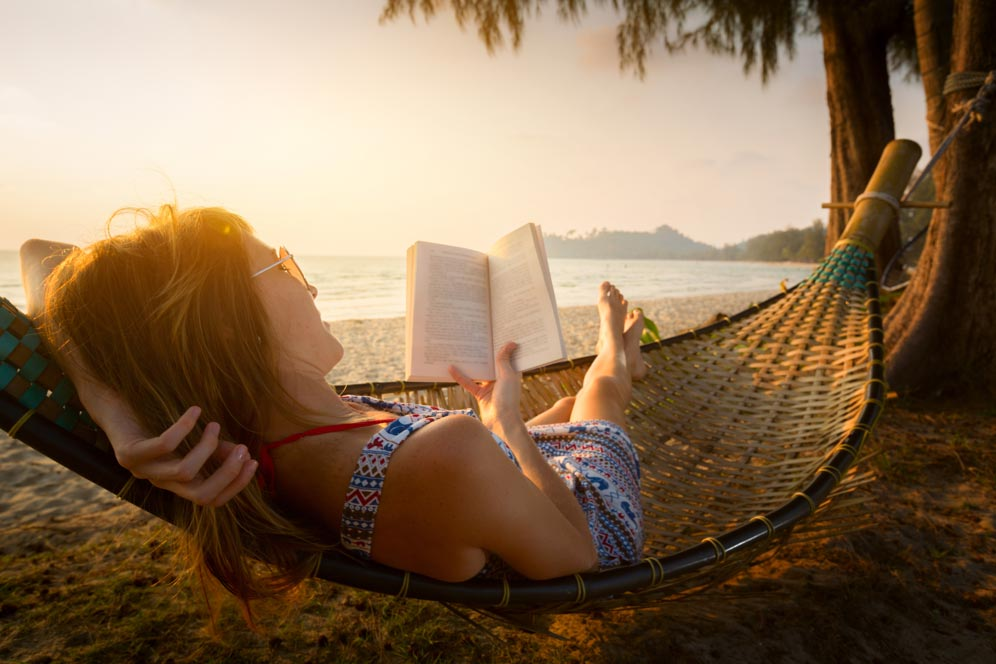 Relaxing in a hammock reading a book on a beach at a singles resort